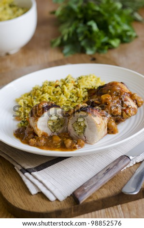 Stuffed chicken thighs in an aromatic spiced tagine sauce with carrot pilau rice - stock photo
