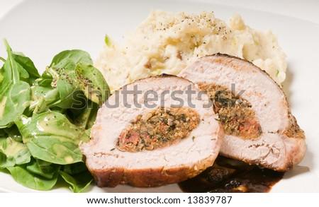 Stuffed Pork Roast with balsamic vinegar and berry reduction, horseradish mashed potatoes,  and baby arugula salad with honey mustard vinaigrette. - stock photo