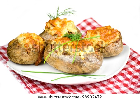 stuffed potatoes covered with cheddar cheese decorated with chives and dill leaves in a white plate - stock photo