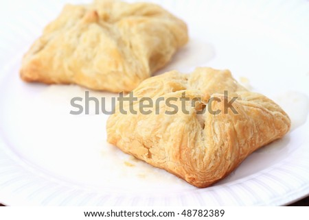 Stuffed puff pastries over a white sauce. Shallow DOF. - stock photo