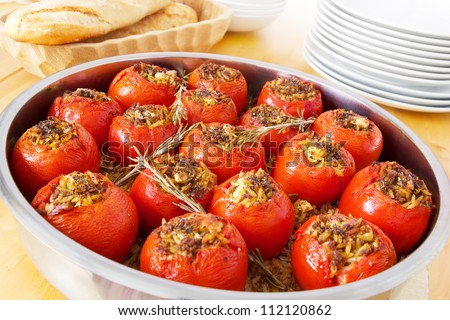 Stuffed tomatoes in a round casserole fresh out of the oven, filled with pasta, mince meat and feta cheese. Decorated with rosemary twigs, bread and dishes - stock photo