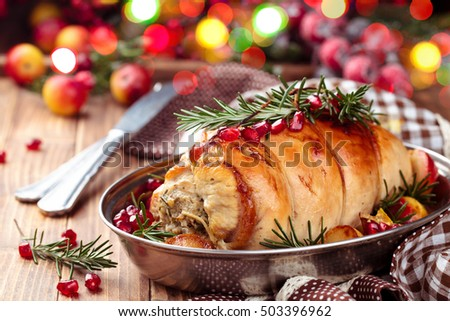 Stuffed turkey breast with baked vegetables and spices against holiday lights background.