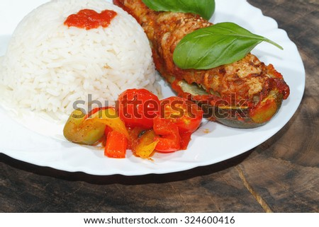 Stuffed zucchini, rice, stewed peppers and tomatoes, vegetables, side dish, garnished with basil leaves on a plate - stock photo