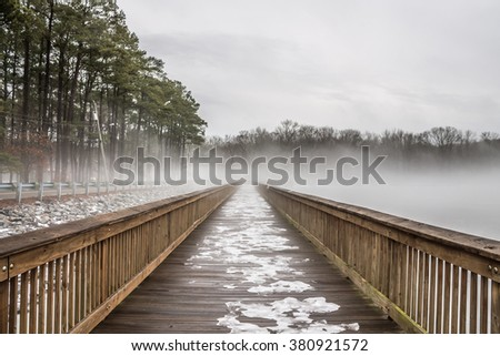 Stumpy Lake fishing pier in snow, ice and fog in Virginia Beach, Virginia.  - stock photo