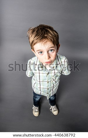 stunned beautiful young 6-year old boy staring with wide-eyed standing for speechless surprise or misunderstanding, high angle view - stock photo