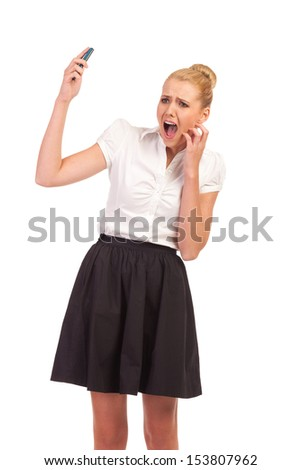 Stunned by loud cell phone. Beautiful young woman with a cell phone shouting. Three quarter length studio shot isolated on white. - stock photo