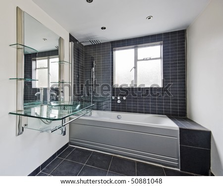 stunning bathroom with modern designer fittings and stone tiles - stock photo