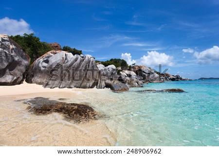 Stunning beach with unique huge granite boulders, turquoise ocean water and blue sky at Virgin Gorda, British Virgin Islands in Caribbean - stock photo