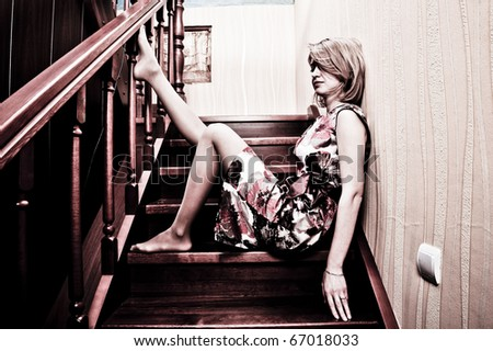Stunning blond beauty sitting on a stairs - stock photo