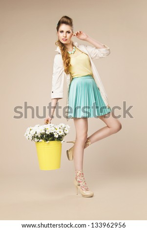 Stunning blonde beauty posing with basket full of flowers on beige background - stock photo