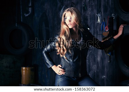Stunning blonde woman in black leather jacket and pants standing in the old garage. - stock photo