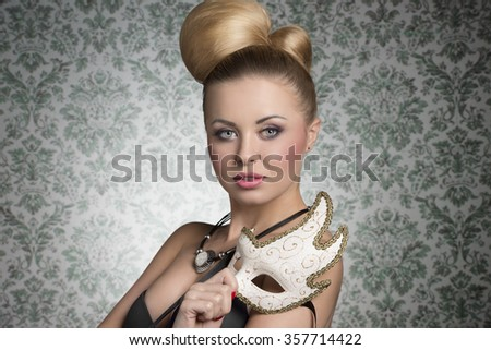 stunning blonde woman with elegant hair-style and necklace posing like a actress with decorated mask in the hand  - stock photo