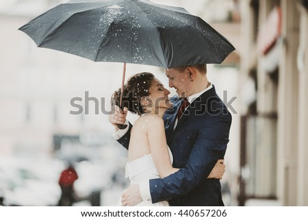 Stunning brunette bride leans to a groom standing under an umbrella - stock photo