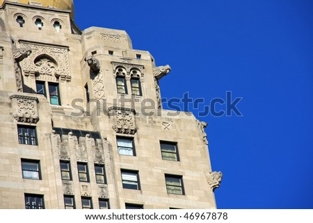 Stunning decorative architecture with birds and gargoyles framed by clear blue sky - stock photo