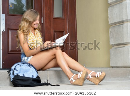 Stunning female college student sits on steps outside building reading textbook - stock photo