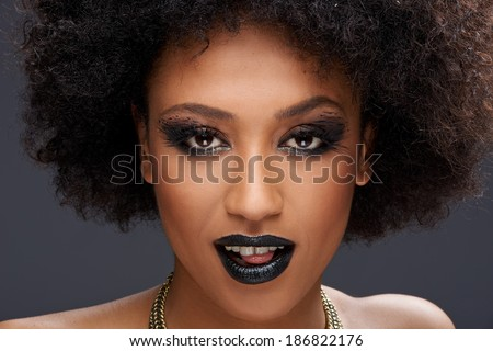 Stunning glamorous African American woman wearing dark makeup looking at the camera with parted lips and the tip of her tongue showing, close up face portrait - stock photo