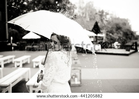 Stunning lady in white holds an umbrella in her arm while rain falls over her - stock photo