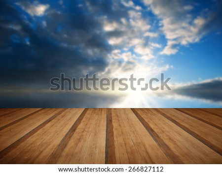 Stunning landscape at sunset reflected in ocean with wooden planks floor - stock photo