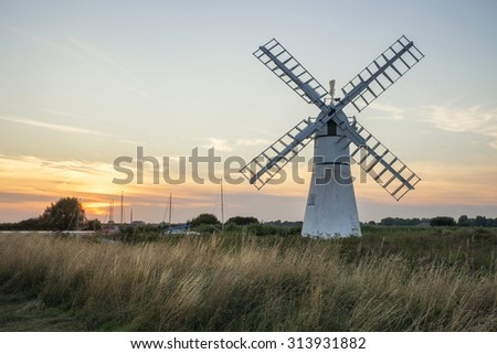 Stunning landscape of windmill and river at sunrise on Summer morning - stock photo