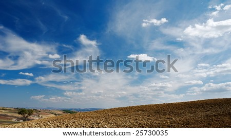 Stunning moody cloudy sky over plowed land