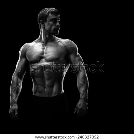 Stunning muscular young men bodybuilder posing and looking behind. Black and white photo - stock photo