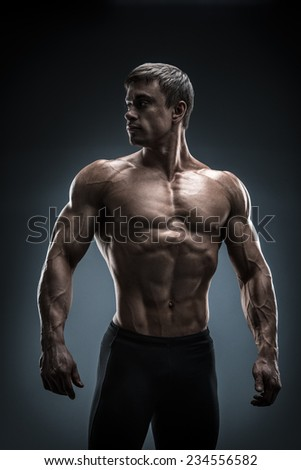 Stunning muscular young men bodybuilder posing and looking behind. Studio shot on black background. - stock photo