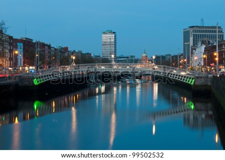 stunning night scene with Ha'penny bridge and Liffey river, the Custom House landmark at the background (picture taken after sunset) - stock photo