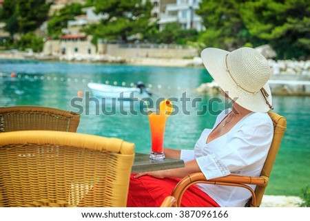 Stunning pretty woman sit in red skirt and white shirt with fruit cocktail on the beach
