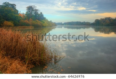 Stunning reflections on lake with light mist and Autumn Fall vibrant colors - stock photo