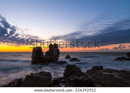 Stunning seascape with part of the old demolished forts in background with blurred waves  in Liepaja, Latvia on the Baltic sea coast while sunset after storm