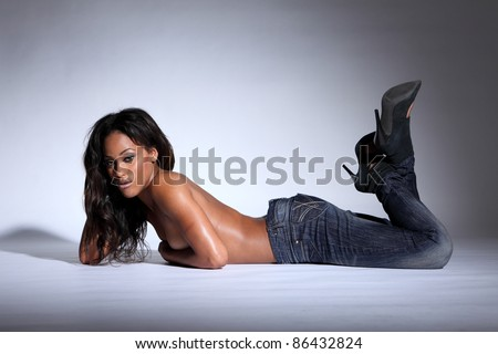 Stunning semi naked young african american woman modelling blue denim jeans, lying in a sexy pose on the floor topless with hands covering her breasts and long dark brown hair. - stock photo