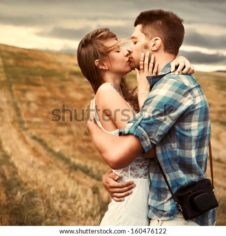 Stunning sensual outdoor portrait of young stylish fashion couple kissing in summer in corn field behind rainy clouds and storm. - stock photo