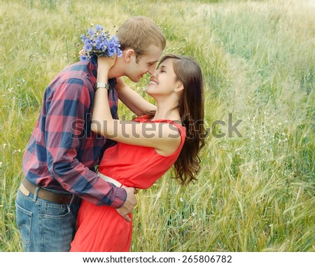 stunning sensual smiling outdoor portrait of young stylish fashion attractive couple in love kissing in summer field - stock photo