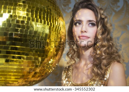 stunning sexy disco woman in gold, surrounded by gold disco balls - stock photo