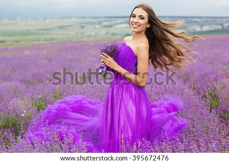 Stunning smiling woman is wearing fashion purple dress holding bouquet of flowers on the nature in lavender field