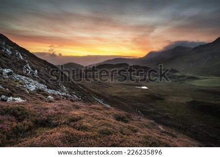 Stunning sunrise mountain landscape with vibrant colors and beautiful cloud formations - stock photo