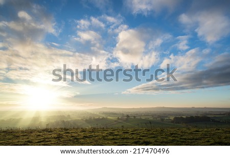 Stunning sunrise over countryside landscape with beautiful Autumn sky - stock photo
