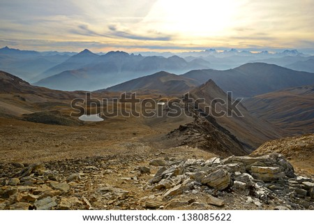 Stunning sunset from the summit of rocky and barren mountains on foggy valleys below. Little lakes reflecting sunlight. Location: western Alps, Torino Province, Italy. - stock photo