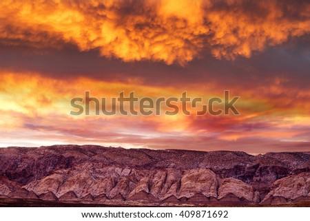 stunning sunset in cloudy sky on mountain range in Utah - stock photo