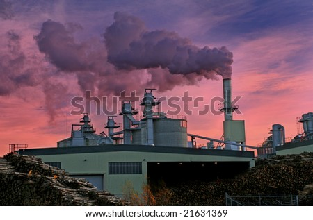 Stunning sunset over Chipboard Factory churning out Gases - stock photo