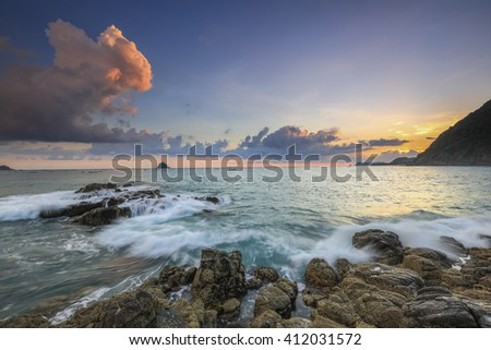 Stunning vibrant sunset over natural rock with strong water wave and sunset background at Selong Belanak Beach, Lombok, Indonesia. Image contain grain, noise and soft focus. - stock photo