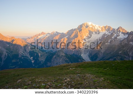 Stunning view at sunrise of Mont Blanc massif (4810 m) and his melting glaciers. Wide angle rear view from from 3000 m in Valle d'Aosta. Summer adventures on the italian french Alps. - stock photo