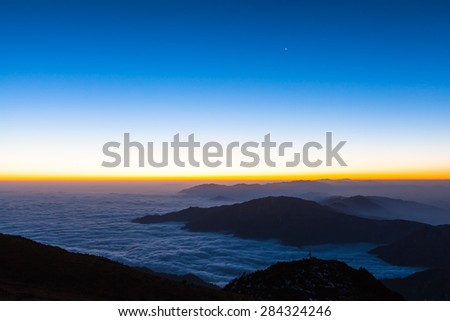 Stunning view before the sunrise with silhouette of mountains and magnificent cloudscape on top of Cattle Back Mountain (Niubeishan) in Sichuan Province, China - stock photo