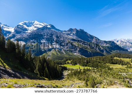 Stunning view of Bluemlisalp and Frundenhorn above Oeschinensee (Oeschinen lake), swiss alps on Bernese Oberland. Photo taken in summer on the hiking path at the lake side, Switzerland - stock photo