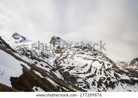 Stunning view of high mountain peaks and glaciers in the italian french alpine arc, in a cloudy day of springtime. Melting snow on the slopes. Morning soft light. - stock photo