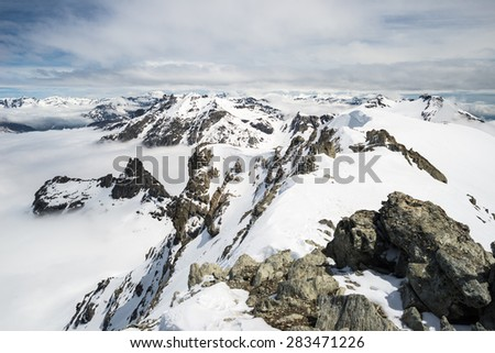 Stunning view of high mountain peaks and snowcapped ridges at high altitude in the italian french alpine arc, in a sunny and cloudy day of springtime. - stock photo