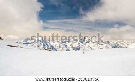 Stunning view of high mountain peaks in the italian alpine arc, in a bright sunny day, with candid fresh snow in the foreground and dramatic sky in the background. - stock photo
