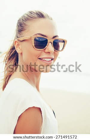 Stunning vintage colorful outdoor summer portrait of pretty young blonde beautiful woman in sunglasses having fun on the beach in windy weather lifestyle trendy colors - stock photo