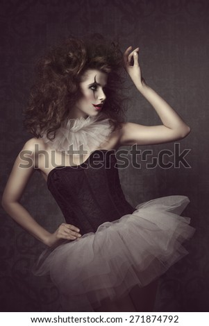 stunning vintage masquerade portrait of sensual brunette woman with vintage gothic tutu, clown make-up and crazy hair-style