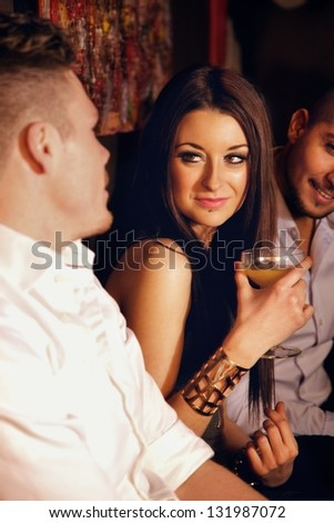 Stunning woman with drinks enjoying the party with male friends - stock photo